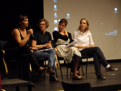 Four women sitting in a row, one is holding a microphone