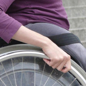 A close picture of a wheelchair wheel with one hand on it.