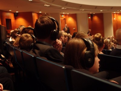 People photographed form behind, sitting in a theatre hall, with headphones on