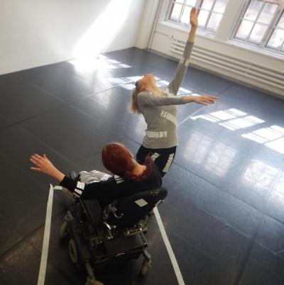 kaksi tanssijaa, toinen pyörätuoia käyttävä, toinen kahdella jalalla kulkeva
