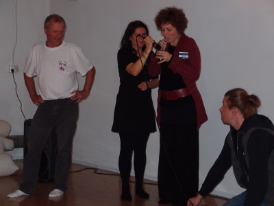 A woman is blowing bubbles to a mug, another woman is holding the microphone in front of the mug. Two men are looking at the woman at both sides, the other one is crouching.