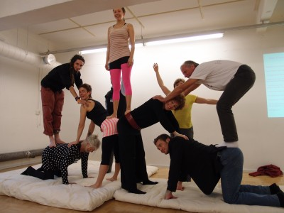 Nine people are making a human pyramid on a matress.