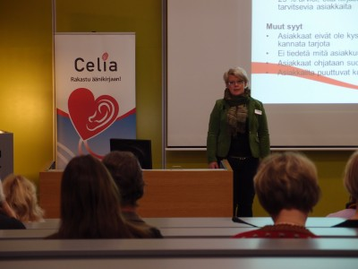 Celia-roll-up vasemmalla, etualalla Minna von Zansen, taustalle heijastettu Power Point