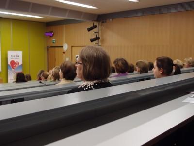Auditorion takariviltä kuvattu nousevassa katsomossa istuvia ihmisiä takaapäin