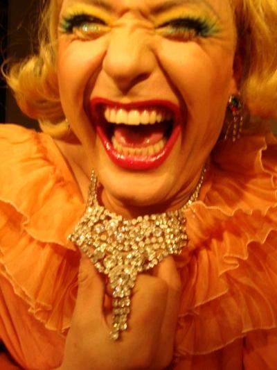 Voimakkaasti meikattu henkilö nauraa kameralle oranssissa puvussa