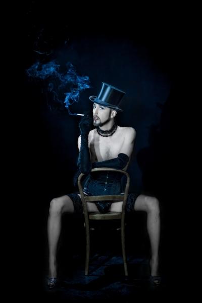 Silinterihattuinen parrakas henkilö tupakoi silkkihansikkaissa ja korkokengissä