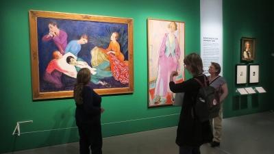 Kolme ihmistä katselee taulua näyttelyssä