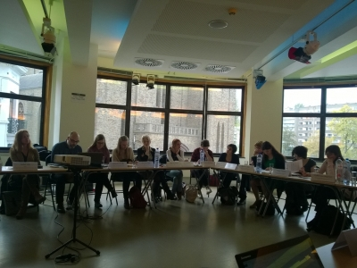 Osallistuja istuvat pöydän ääressä