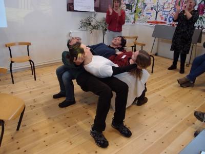 Neljä ihmistä nojaa toisiinsa istuen, kun tuolit on poistettu heidän altaan