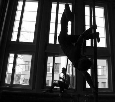 Mustavalkoisessa kuvassa mies roikkuu ylösalaisin tangossa ja toinen soittaa saksofonia ikkunalaudalla