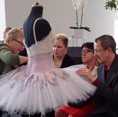 People sitting in a circle and touching a pink ballet costume