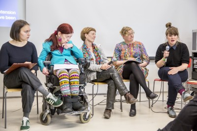 Viisi naista istuu vierekkäin paneelissa
