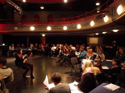 Teatterimainen tila, jossa seminaarin yleisö kuuntelee