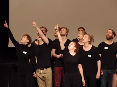 Näyttelijät seisovat ryppäässä ja osoittavat kohti taivasta