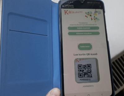 Kulttuurikäyttäjä lukee QR-koodin älypuhelimella